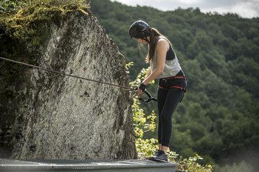 Germany, Westerwald, Hoelderstein, woman climbing on via ferrata - PAF001559