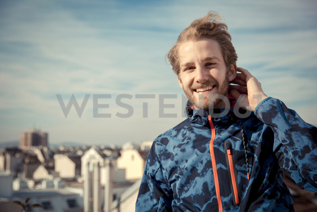 Portrait of smiling young man on a roof - SUF000059