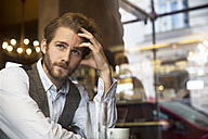 Young man in a cafe looking out of window - SUF000062