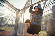 Young man helping girlfriend doing chin-ups - SUF000071