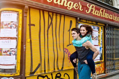 Young man carrying girlfriend in the city - SU000074