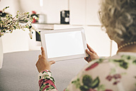 Over the shoulder shot of elderly woman using a tablet computer at home - MFF002724