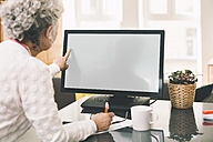 Over the shoulder shot of elderly woman using a desktop computer at home - MFF002727