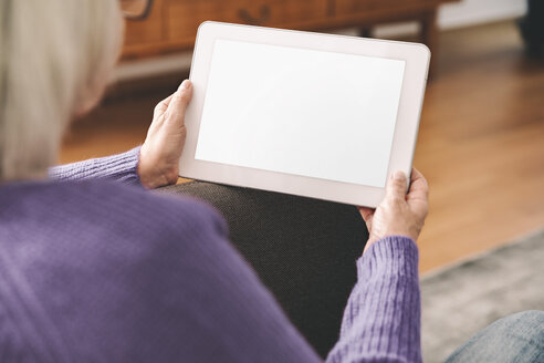 Over the shoulder shot of elderly woman using a tablet computer at home - MFF002730