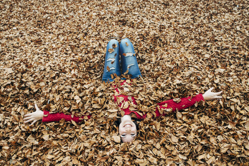 Woman with arms outstretched lying on forest soil covered with autumn leaves - GEMF000765