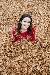 Portrait of smiling woman sitting on forest soil covered with autumn leaves - GEMF000768