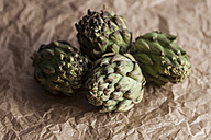 Four artichokes on crumpled brown paper - VABF000248