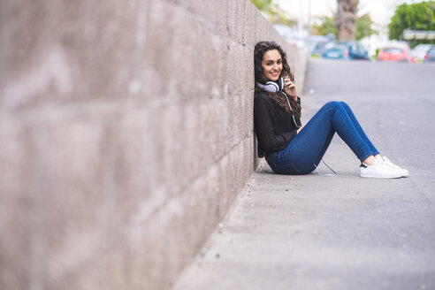 Portrait of smiling teenage girl with headphones sitting on the ground - SIPF000218