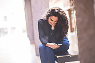 Smiling teenage girl sitting on a bench looking at hersmartphone - SIPF000224