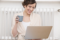 Happy woman at home using laptop - FMKF002427