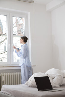 Woman in bedroom looking out of window - FMKF002433