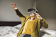 Awed woman wearing virtual reality glasses using her hands - MFF002745