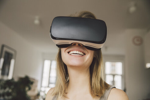 Laughing woman wearing virtual reality glasses - MFF002748