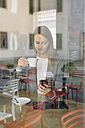 Young woman in a cafe looking at cell phone - ALBF000032