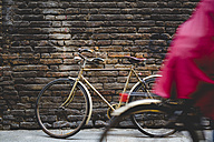 Vintage bicycle leaning against a brick wall while cyclist passing by - GIOF000787