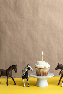 Cup cake with lighted candle on a cake stand and four toy horses besides - VABF000285