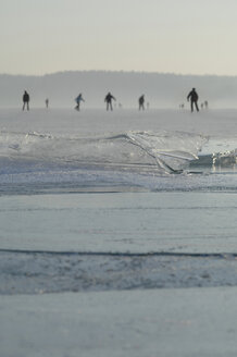 Germany, people ice skating on frozen lake with thin ice sheet - CRF002744