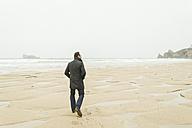 France, Bretagne, Finistere, Crozon peninsula, man walking on the beach - UUF006646