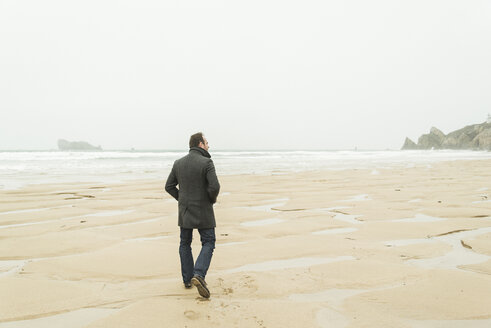France, Bretagne, Finistere, Crozon peninsula, man walking on the beach - UUF006646