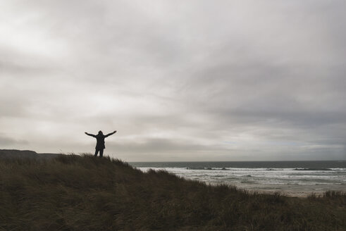 France, Bretagne, Finistere, Crozon peninsula, man standing at the coast under cloudy sky spreading out his arms - UUF006649