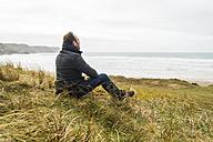 France, Bretagne, Finistere, Crozon peninsula, man sitting at the coast - UUF006652