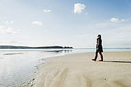France, Bretagne, Finistere, Crozon peninsula, woman walking on the beach - UUF006658