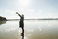 France, Bretagne, Finistere, Crozon peninsula, woman taking a selfie on the beach - UUF006661