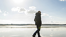 France, Bretagne, Finistere, Crozon peninsula, man walking on the beach - UUF006664