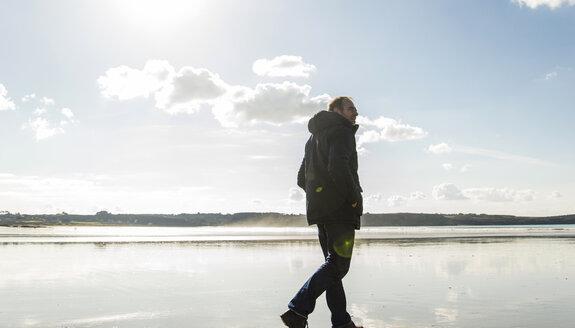 France, Bretagne, Finistere, Crozon peninsula, man walking on the beach - UUF006664