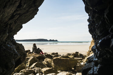France, Bretagne, Finistere, Crozon peninsula, woman sitting on the beach as seen from rock cave - UUF006673