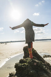 France, Bretagne, Finistere, Crozon peninsula, woman balancing on rock on the beach - UUF006676