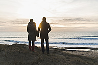 France, Bretagne, Finistere, Crozon peninsula, couple standing at the coast at sunset - UUF006688