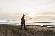 France, Bretagne, Finistere, Crozon peninsula, man walking at the coast at sunset - UUF006691