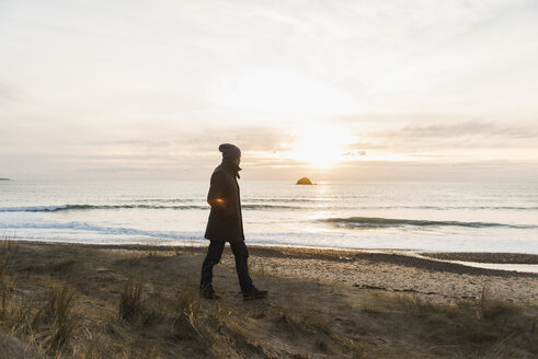 France, Bretagne, Finistere, Crozon peninsula, man walking at the coast at sunset - UUF006691