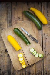 Whole and sliced yellow and green zucchini on wood - LVF004608