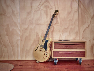 Electric guitar leaning on chest of drawers - RHF001295