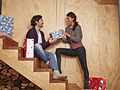 Happy couple sitting on wooden stairs holding Christmas presents - RHF001310