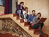 Friends sitting on wooden stairs using laptop - RHF001313