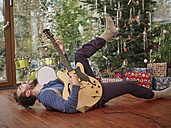 Man playing electric guitar in front of Christmas tree - RHF001316