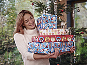 Woman carrying stack of Christmas parcels - RHF001322