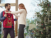 Couple standing in front of Christmas tree trying on Christmas jumper - RHF001325