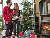 Happy couple in front of Christmas tree wearing Christmas sweaters - RHF001331