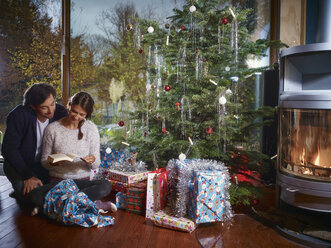 Couple reading book under Christmas tree - RHF001337