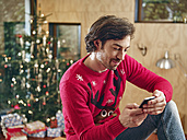 Man using smart phone in front of Christmas tree - RHF001343
