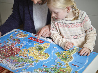 Father and daughter playing with world map jigsaw puzzle - RH001370