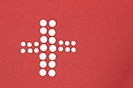 Cross shape of white tablets on red ground - CMF000362