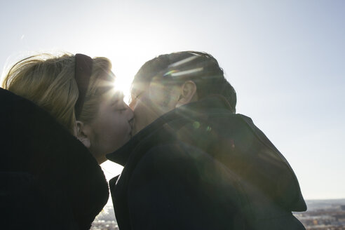 Young couple kissing at backlight - ABZF000248