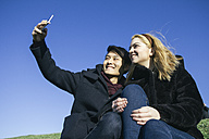Young couple taking a selfie with smartphone - ABZF000251