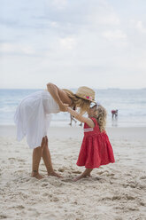 Brasil, Rio de Janeiro, mother kissing daughter on Copacabana beach - MAUF000272