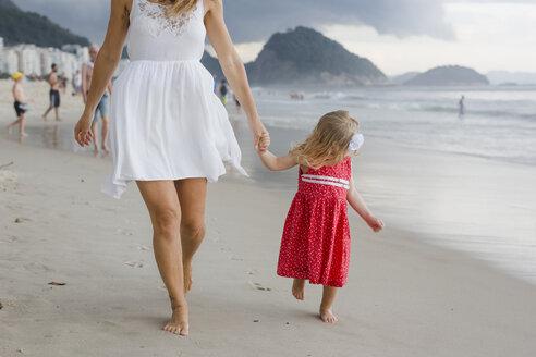 Brasil, Rio de Janeiro, mother and daughter walking on Copacabana beach - MAUF000275